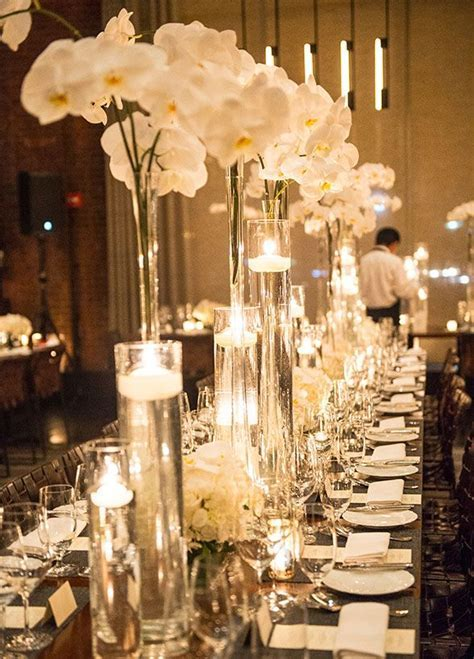 wedding table decor  Tall glass vases are lush with white