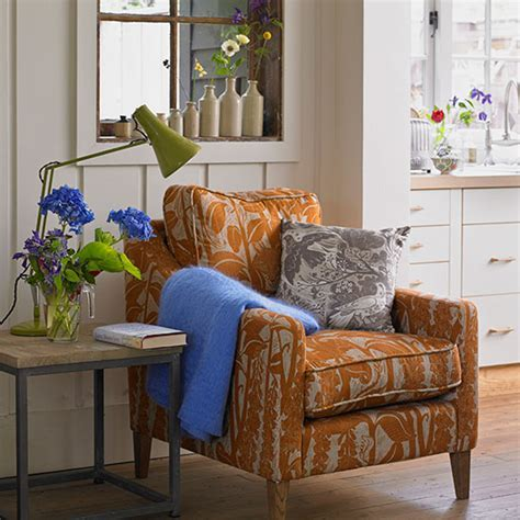 Cream living room with burnt orange armchair   Decorating
