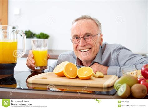 The Juice Kitchen by Smiling Senior With A Glass Of Orange Juice