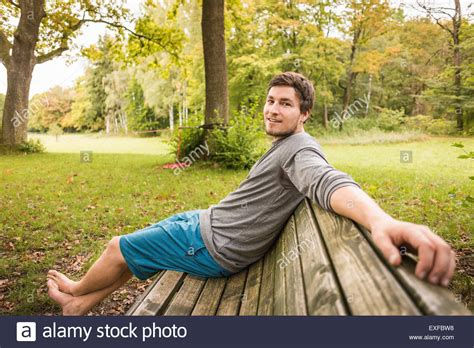 sitting on park bench portrait of barefoot young man sitting on park bench stock