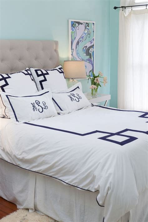 white comforter with blue trim gray button tufted headboard white sheets with blue trim