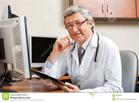 Sitting On A Medicine At Desk doctor sitting at desk in front of computer stock