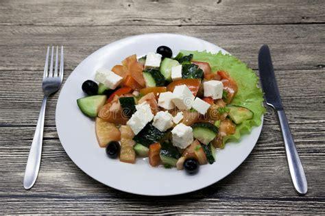 2501116569 un couteau un plat une salade grecque d un plat blanc avec la fourchette et de