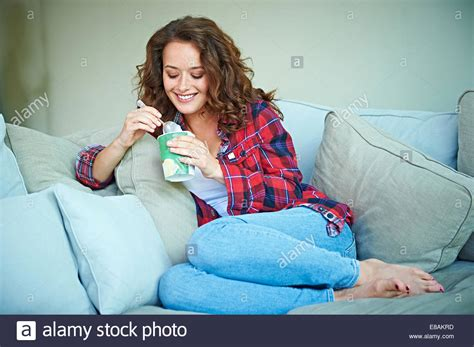 woman eats couch woman eating ice cream on sofa stock photo royalty free