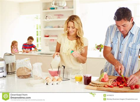 family in kitchen parents preparing family breakfast in kitchen stock photo