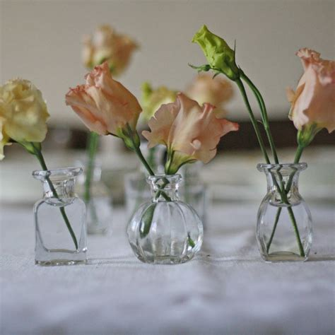 grouping of six tiny glass bottle vases for weddings by