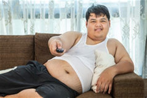 fat guy on couch overweight guy sitting on the couch to watch some tv