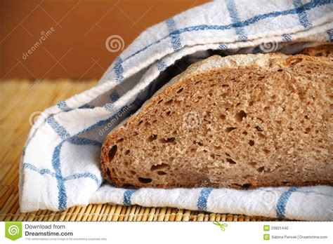 Loaf Handcrafted Breads - halved rye bread loaf wrapped in the kitchen towel stock