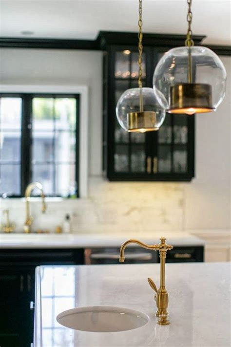 black kitchen cabinets white counters brass gold faucet