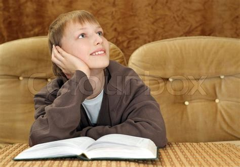 boy on couch beautiful caucasian boy sitting on the couch with a book