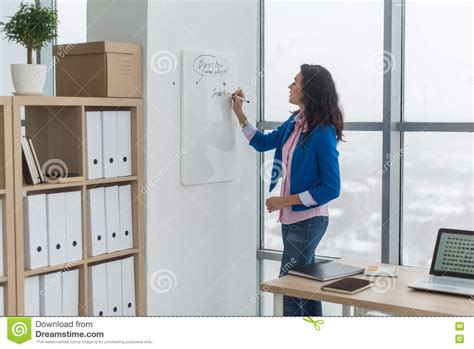 Bor Magnet Modern businesswoman writing day plan on white board modern office side view of caucasian