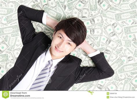 bed full of money happy businessman lying on money bed stock photo image
