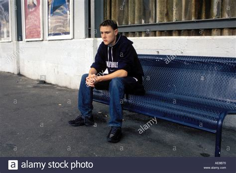 bench for sitting 14 year old boy looking fed up depressed sitting on bench