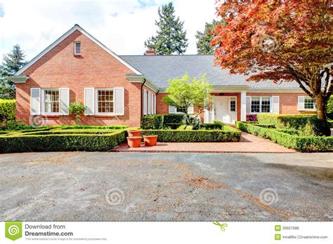 house with white shutters brick red house with english garden and white window shutters royalty free stock