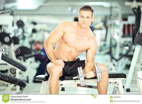 Fits Power Lifting Fitness Lifting Fitness shirtless muscular on a bench lifting weight in a