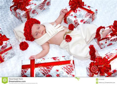 newborn baby boy santa claus with christmas gifts stock