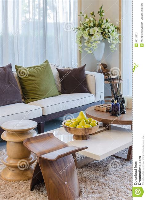 living room with wooden furniture and flower stock photo