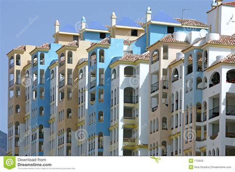 row of colorful apartments in spain stock photos