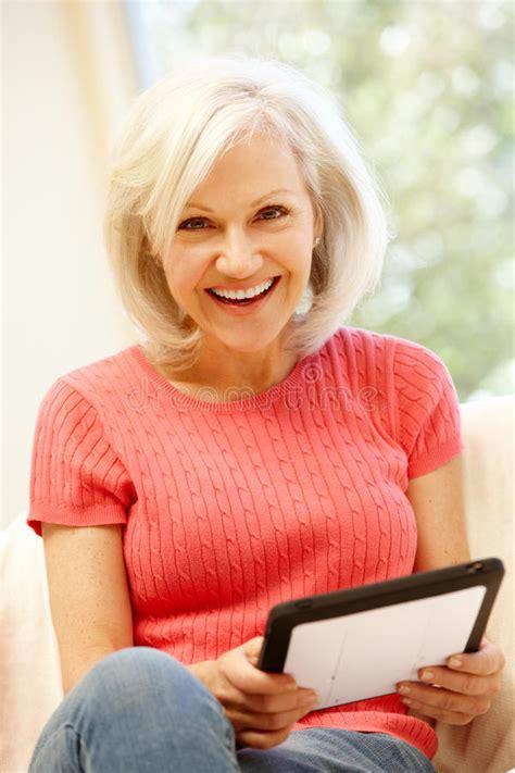 einkaufen zu hause mittlere altersfrau die zu hause tablette verwendet