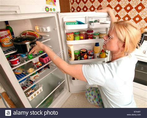 into the food putting food into the fridge in the kitchen stock photo royalty free image