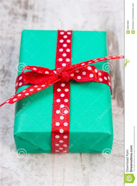green gift for christmas or other celebration on wooden