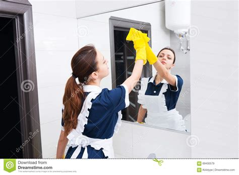 maid in bathroom maid cleaning bathroom mirror with sponge stock image