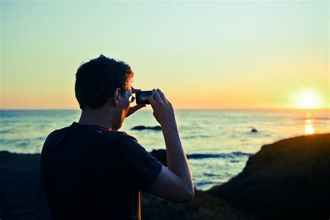 taking pictures taking a picture of the sunset with his iphone juozas