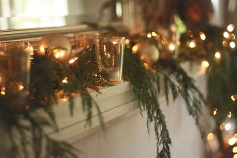 garland and christmas lights on fireplace emerald