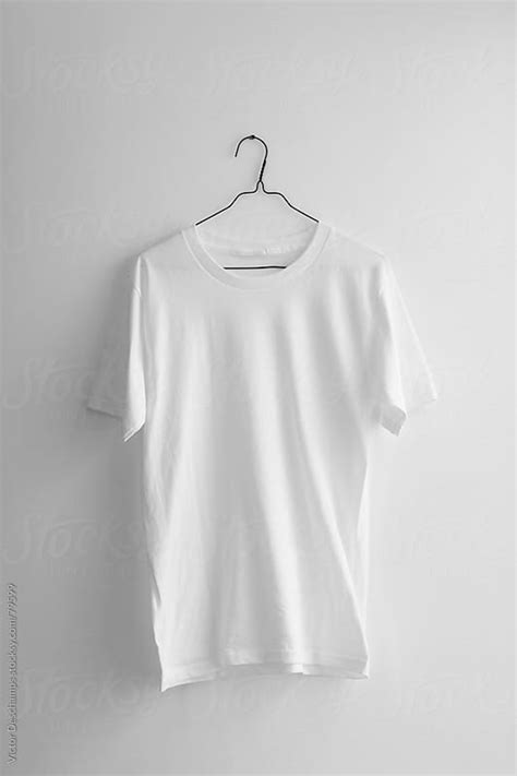 Tshirt Kaos Ages plain white t shirt hanging on the wall by victor