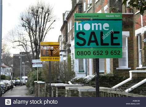 house sales uk estate agent house for sale signs in street in london uk