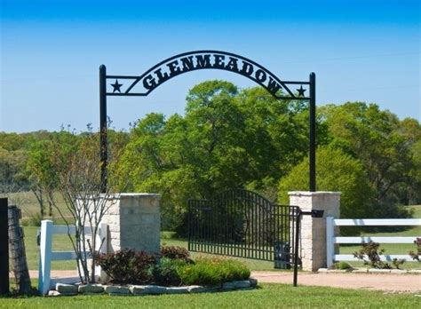 ranch names big columns supporting an arched name plate of ranch with simple garden on