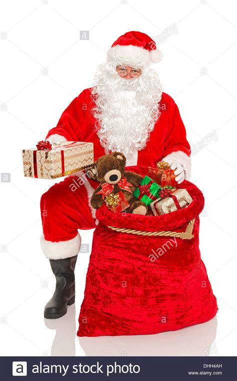 santa claus or father christmas handing out gifts from his