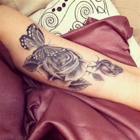 rose tattoo with butterfly posts grey ink and butterfly on biceps grey