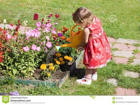 girl watering flowers girl watering flower beds royalty free stock photos