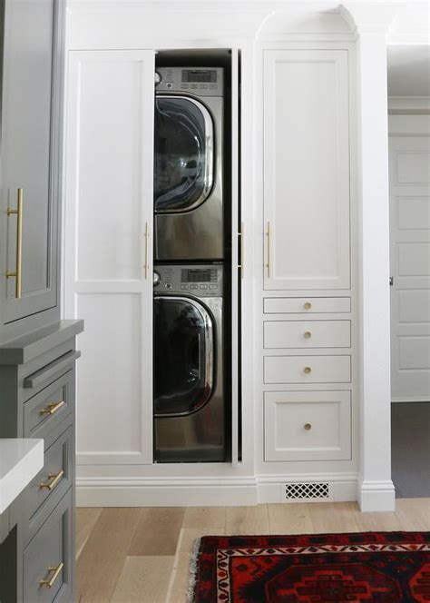Beautiful laundry room features hidden stacked washer and dryer