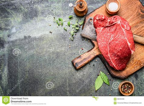 piece of excellent raw meat on cutting board with herbs