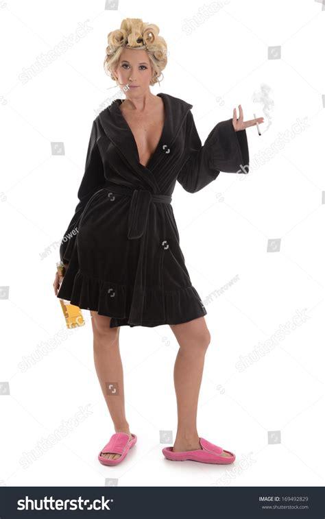 In The Bedroom Trailer woman cigarette liquor bottle bath robe stock photo
