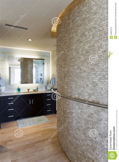 Bathroom Towel Ideas bathroom with curved stone wall and cabinets royalty free