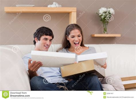 couch couple couple on the couch opening parcel royalty free stock