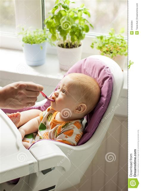 Sits In Chair To Eat by Baby Sitting In His Chair And From Spoon Stock
