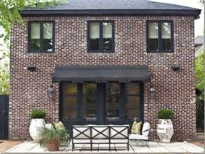 black widow awning brick roof black window frames exterior