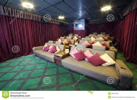 theatre with couches couches with cushions and projector in small movie theate
