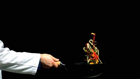 chef background chef tossing vegetables in a wok black background in