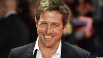 British actor hugh grant poses for pictures on the red carpet as he