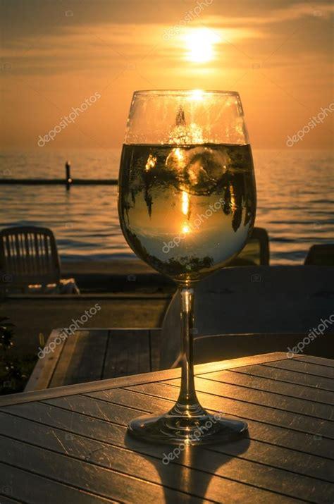 foto bicchieri di vino bicchiere di vino e tramonto in riva al mare foto stock