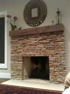 stacked stone fireplace with rustic wood mantle for living