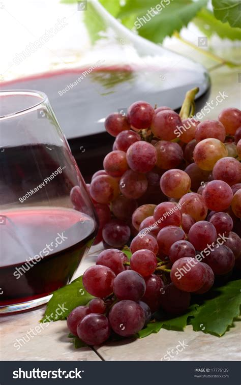 glass of red wine decanter and fresh cut black wine grape