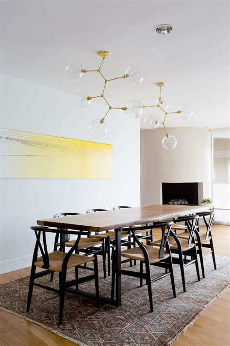 earthy modern dining room  gold light fixture black wishbone chairs  edge dining table