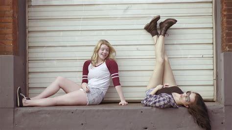 teen girl hanging upside down 2 blonde teens hang upside down on rock wall hold hands
