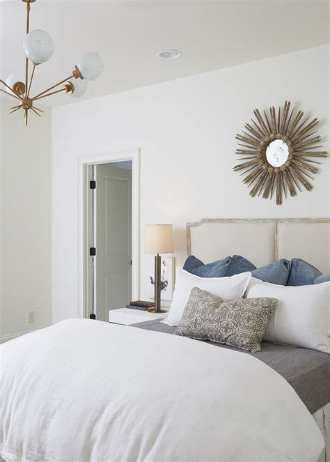 white bedroom walls french gray headboard with gold sunburst mirror
